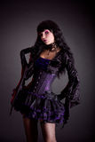 Beautiful witch in purple and black gothic Halloween outfit Stock Photos