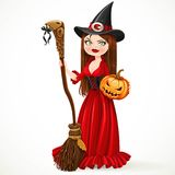 Beautiful witch in a red dress holding a broom for flying Royalty Free Stock Photography