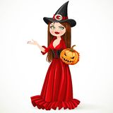 Beautiful witch in a red dress holding a pumpkin Royalty Free Stock Images