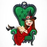 Beautiful witch in red dress sitting in armchair with high back Royalty Free Stock Photos