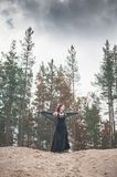 Beautiful witch with red hair standing on the hill royalty free stock photo