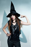 Beautiful witch stands and shows hat Stock Image