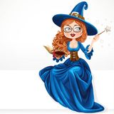 Beautiful witch wearing in blue dress holding a magic wand Royalty Free Stock Photos