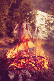 Beautiful witch in the woods near the fire. Magic woman celebrat Royalty Free Stock Photos