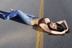 Beautiful woamn laying in road Stock Photography