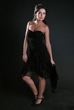Beautiful woman. The fine woman in an evening dress on a black background Stock Photography