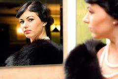 Beautiful woman. Beautiful luxurious woman looks at her reflection Stock Photo