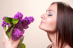 The beautiful woman. Smells summer bouquet of lilac Royalty Free Stock Photography
