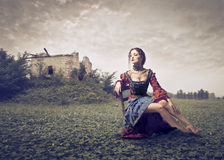Beautiful Woman. Sitting on a chair in a large lawn Royalty Free Stock Photos