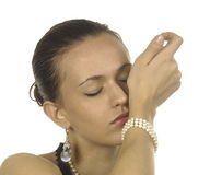 Beautiful woman. Beautiful young woman wearing pearls sniffing at perfume on wrist with eyes closed Royalty Free Stock Photography