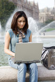 Beautiful woman. A portrait of a beautiful young woman working on her laptop outdoor Royalty Free Stock Photography