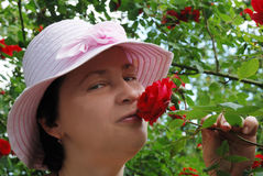 Beautiful woman. A woman in a pink hat smells a rose Royalty Free Stock Photography