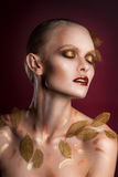 Beautiful  woman in accessories with gold leaves Stock Photo