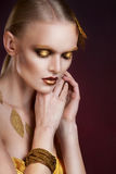 Beautiful  woman in accessories with gold leaves Stock Images