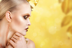 Beautiful  woman in accessories with gold leaves. Royalty Free Stock Photography