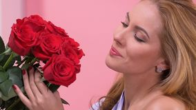 Beautiful woman admiring bouquet of red roses, surprise for Valentines day