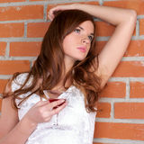 Beautiful woman against brick wall Royalty Free Stock Images