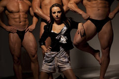 Beautiful woman against three athletes Stock Photo