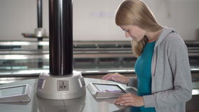Beautiful woman in airport terminal near electrical chargers. Using touchscreen, searching information. Beautiful attractive young woman in airport terminal near stock footage