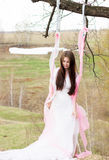 Beautiful woman in all white wedding dress on sunny day outdoors swing Stock Photography