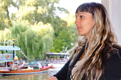 Beautiful woman alongside a lake with boats Royalty Free Stock Photos