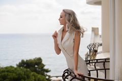 Woman with long hair in amazing clothes. Beautiful woman in amazing clothes posing in hotel royalty free stock images