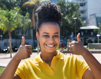 Beautiful woman with amazing hairstyle showing both thumbs up Royalty Free Stock Photo