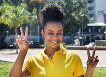 Beautiful woman with amazing hairstyle showing victory sign Royalty Free Stock Image