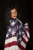 Beautiful woman with American flag draped on shoulder looking do Royalty Free Stock Images