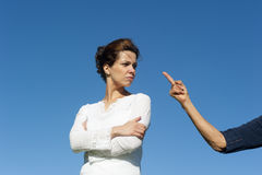 Beautiful woman in anger facing accusation. A pretty looking young woman with an angry and stubborn facial expression looking at an in accusation pointed arm Stock Photography