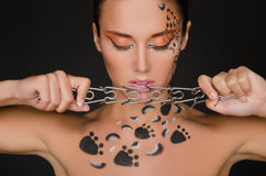 Beautiful woman with animal figures keeps collar Stock Images