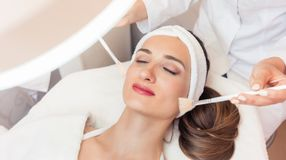 Beautiful woman during anti-aging facial massage in a modern cos stock photo