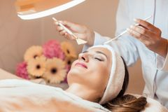 Beautiful woman during anti-aging facial massage in a modern cosmetic center stock image