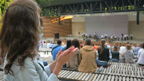 Beautiful woman applauding at the open air concert during summer. 4k stock footage