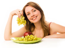Beautiful woman with an apple and grapes royalty free stock photo