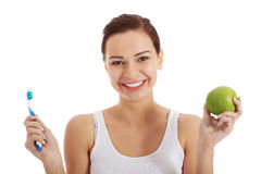 Beautiful woman with apple and toothbrush. Stock Image