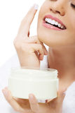 Beautiful woman applies face cream. Stock Photos