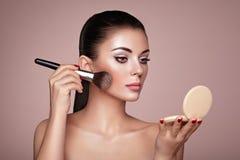 Beautiful Woman applies Skin Tone with Brush Stock Image