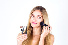 Beautiful woman apply blush on face with smile. Make-up artist. Stock Photo