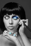 Beautiful woman applying blue eye makeup. black Stock Photos