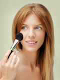 Beautiful woman applying blush with brush Stock Images