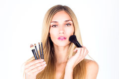 Beautiful woman applying blush on the face. Make-up artist. Stock Photography