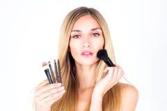 Beautiful woman applying blush on the face. Make-up artist. Young beautiful woman applying blush on the face. Make-up artist Stock Photography