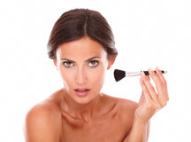 Beautiful woman applying blush on her face Royalty Free Stock Images