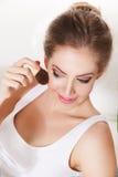 Beautiful woman applying blush Stock Images