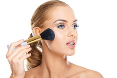 Beautiful woman applying blusher Royalty Free Stock Photos