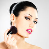 Beautiful woman applying blusher on face Royalty Free Stock Photos