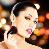 Beautiful woman applying blusher on face Stock Photos
