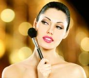 Beautiful woman applying blusher on face Royalty Free Stock Photo