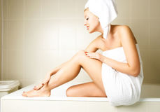 Beautiful woman applying body lotion Stock Photography